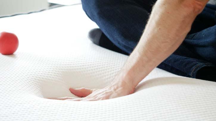 A man presses into a foam mattress.