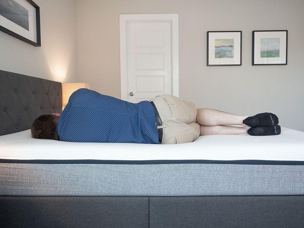A man lies on his side on a mattress.