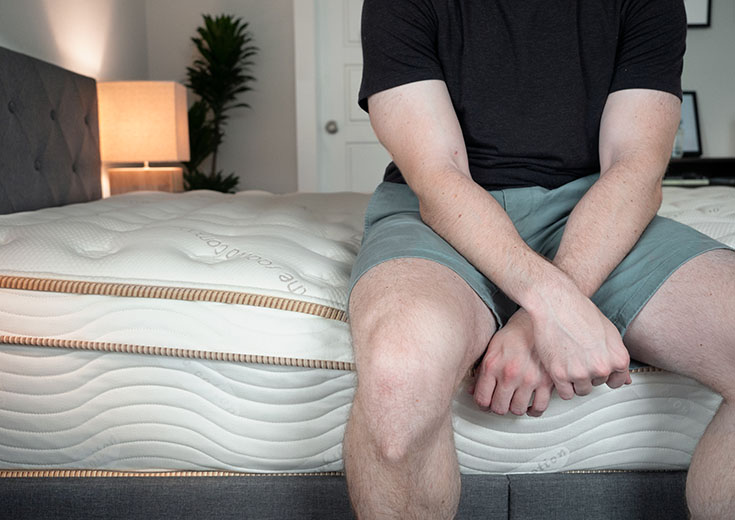 A man sits near the edge of his bed.