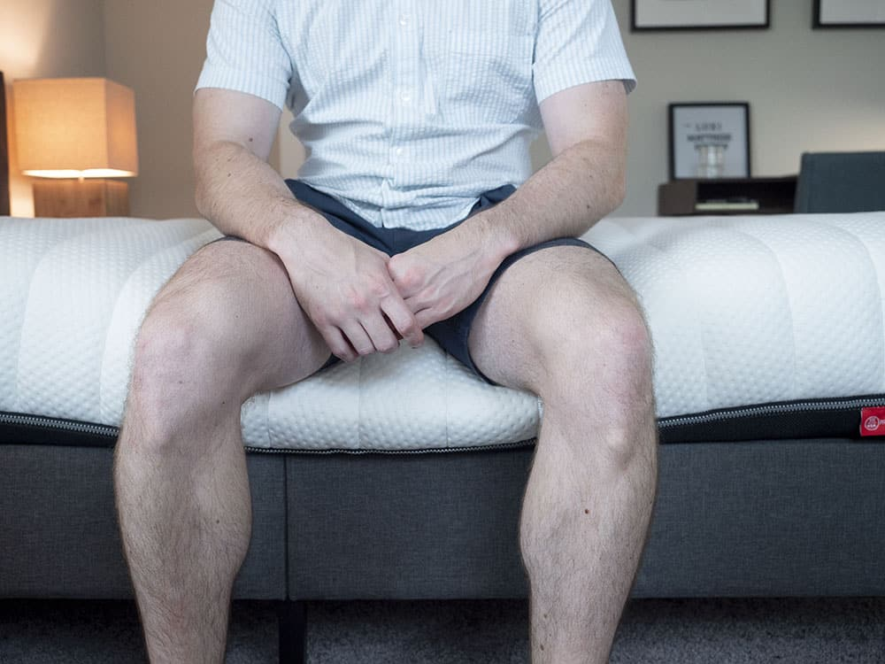 A man sits on the edge of the bed.