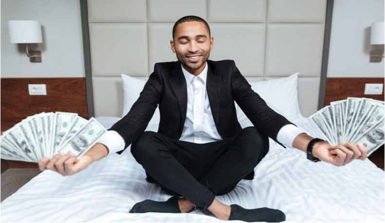 A man sits on his bed holding money.