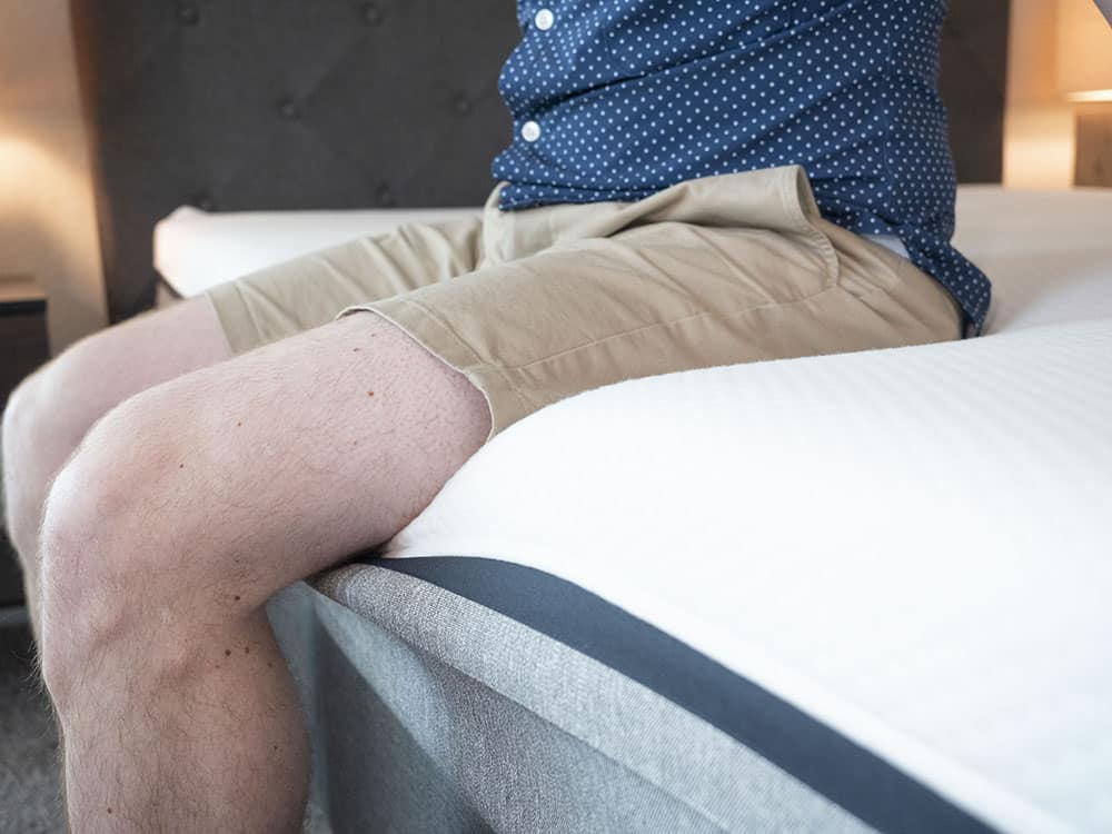 A man in shorts sitting near the edge of a mattress.