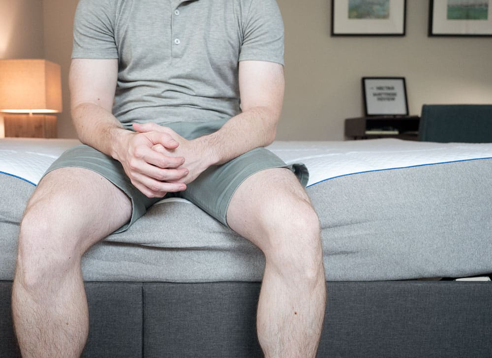 A man sits near the edge of the bed.
