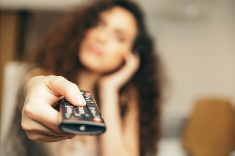 A woman holds a remote control.