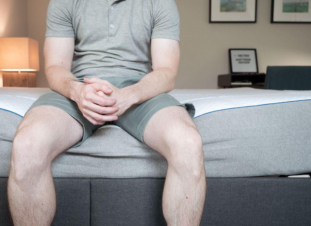 A man sits on a mattress.