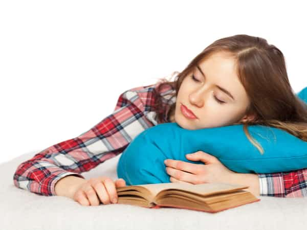 A young girls rests with a book.