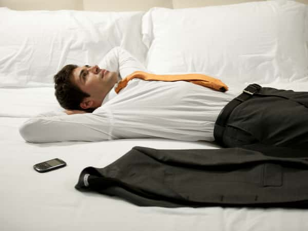 A well dressed man lies on a hotel bed.
