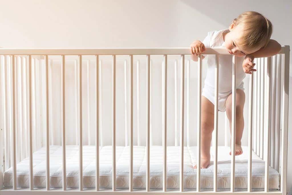 Toddler hanging out of crib