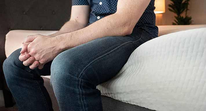 A man sits down on his mattress.