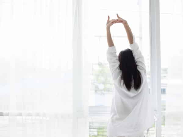A woman stretches in the morning.