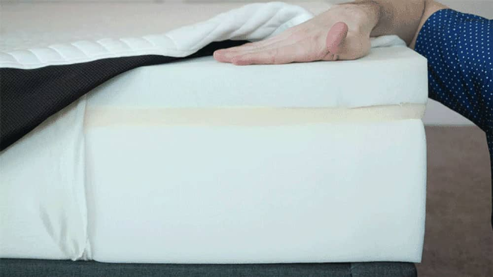 A mattress is opened to show its components.