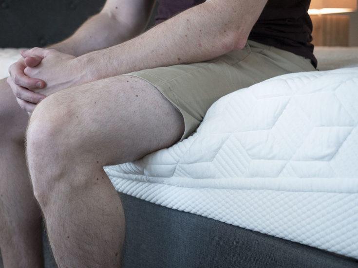 A man sits near the edge of the mattress.