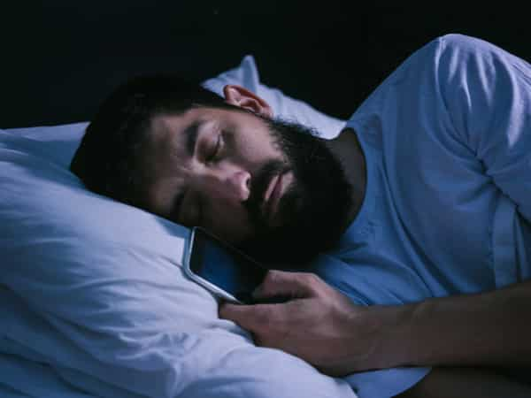 A man holds his phone while he sleeps.