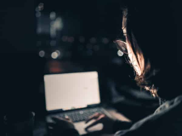 A man looks at his computer in the dark.