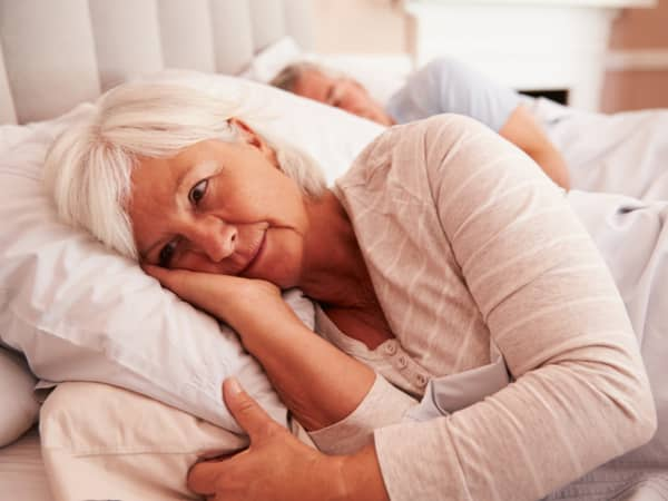 An older woman lies in bed awake.