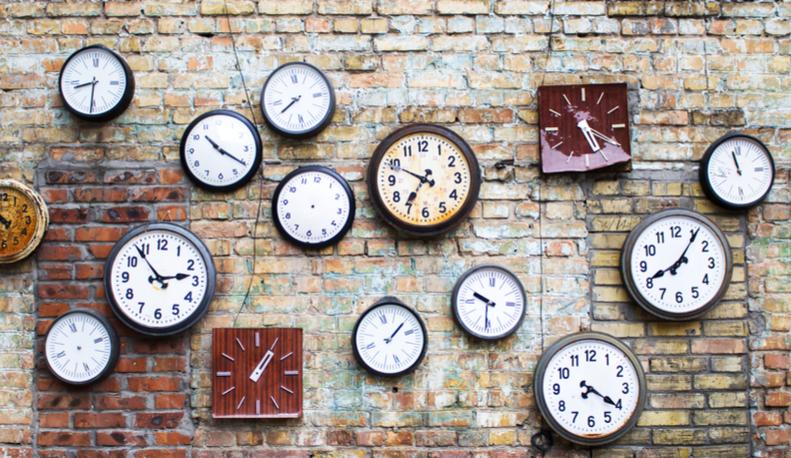 A wall of clocks on brick.