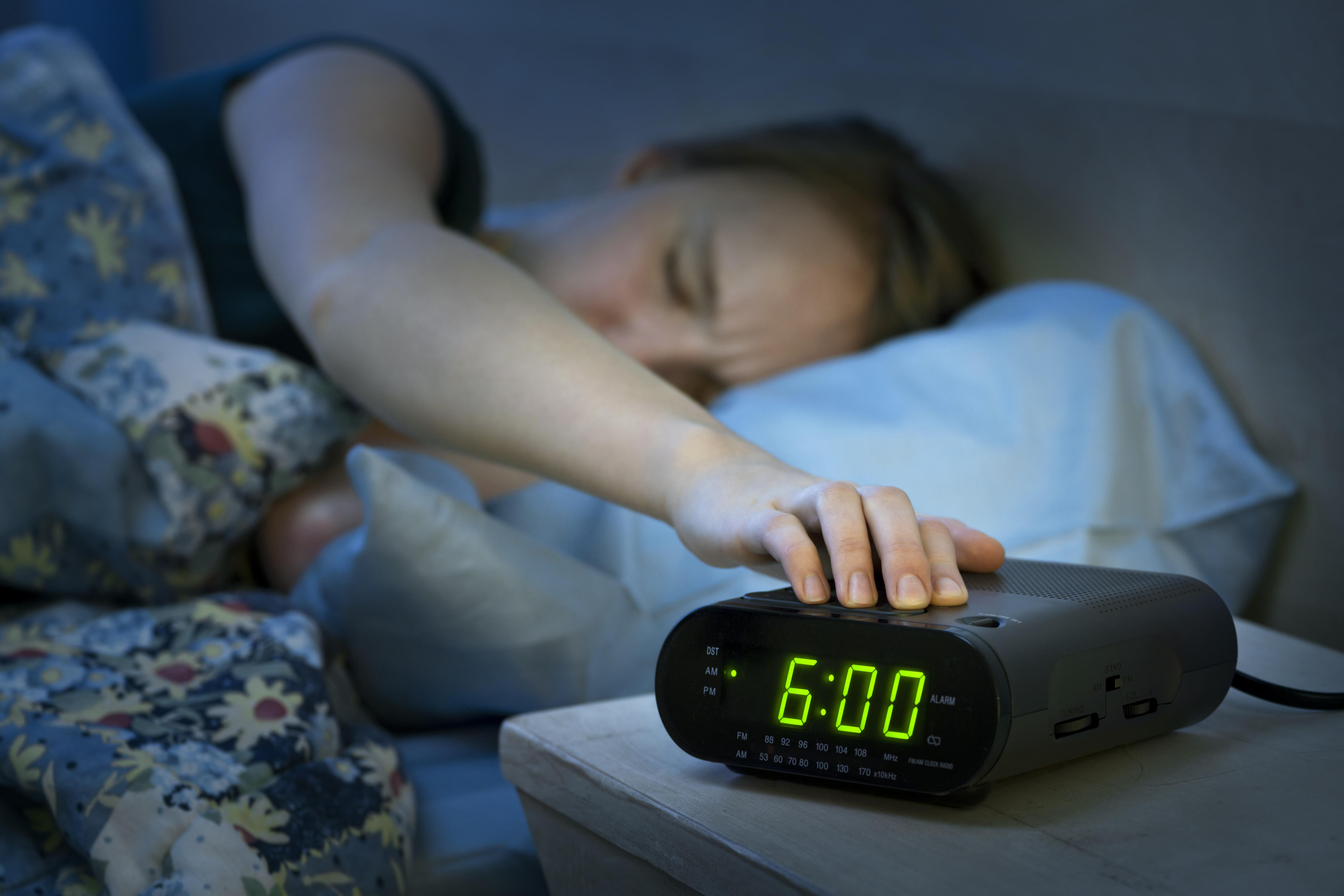 tired woman hitting alarm clock