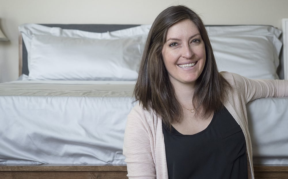 woman smiling in front of bed