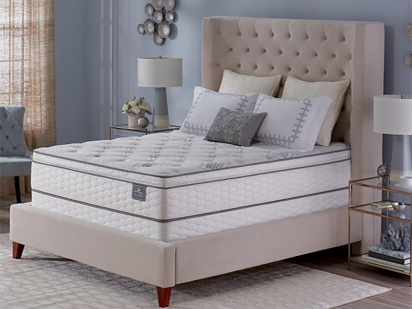 A mattress sits in an upscale bedroom.