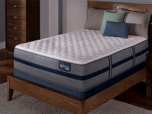 A mattress sits on a wooden frame.