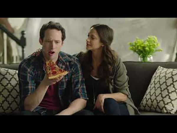 man and woman on couch with man eating pizza