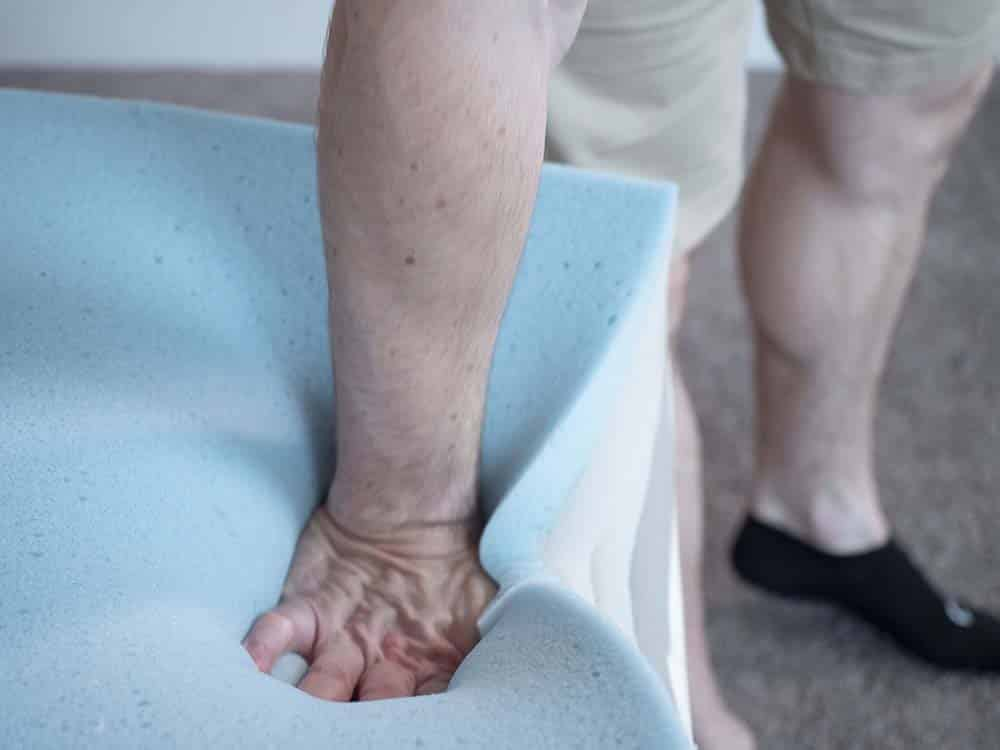 Man pressing down on foam layers in mattress