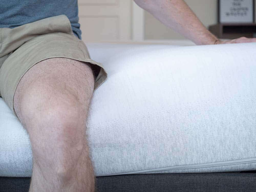 Man sitting on the edge of a mattress