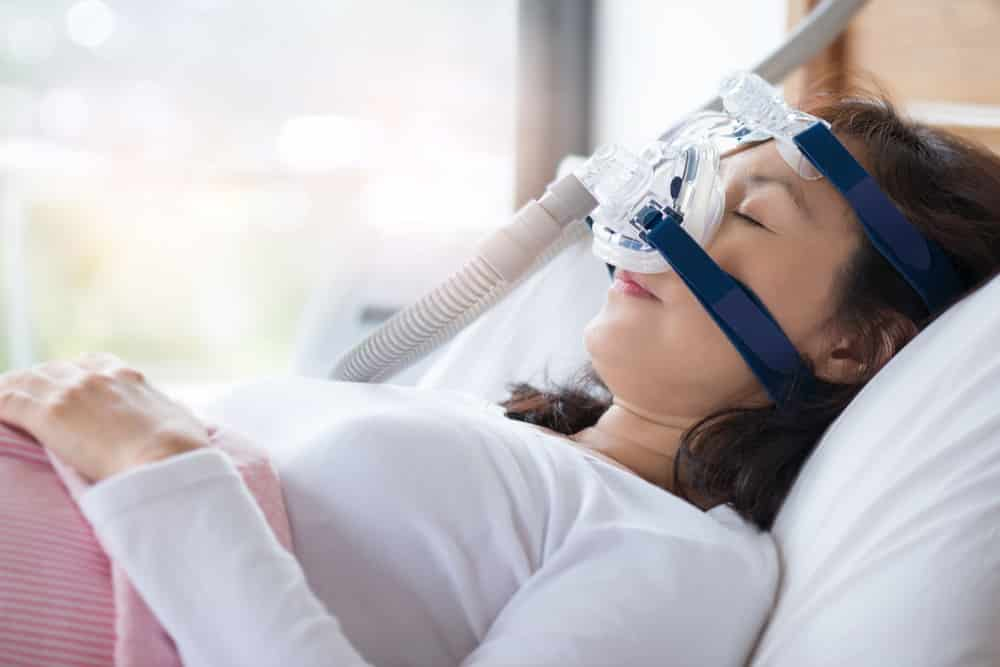 A woman sleeps with a sleeping machine