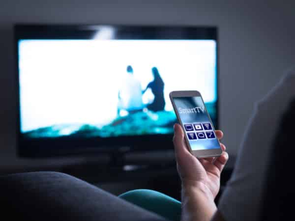 television on with a person watching holding a smartphone