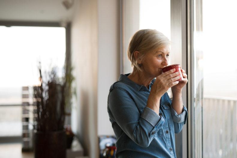 Woman drinking coffee at window