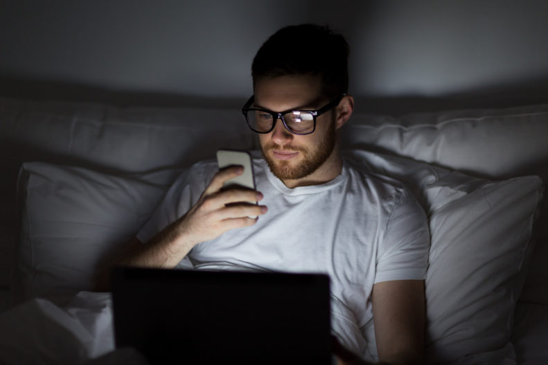 Man looking at screens in bed