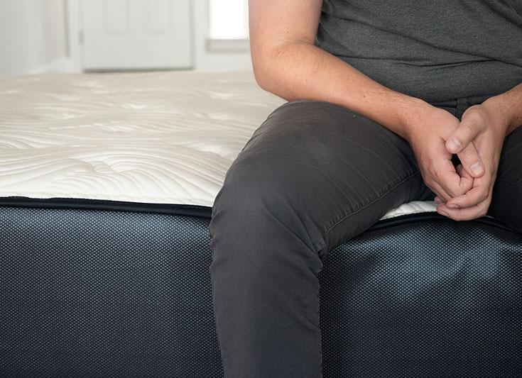 A man sits near the edge of a mattress.