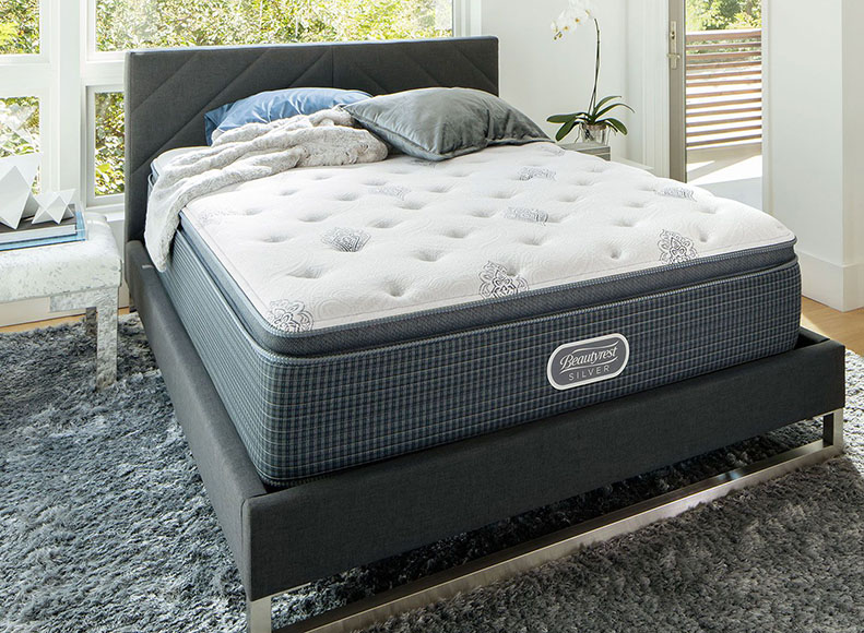 A mattress is shown in a nice bedroom.