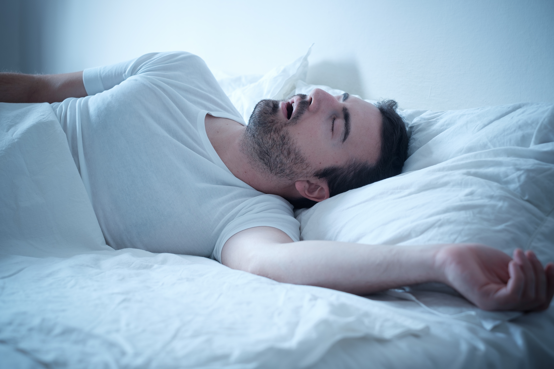 Man sleeping on bed snoring
