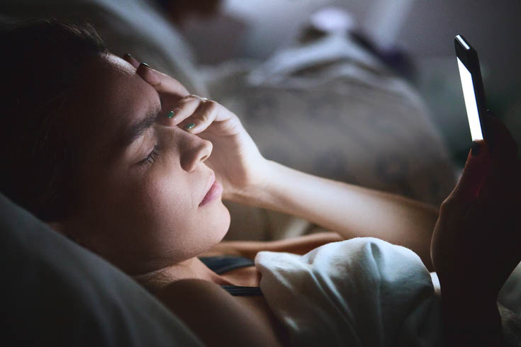 A woman looks at her phone in bed.