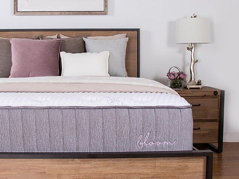 A hybrid mattress on a wooden foundation.