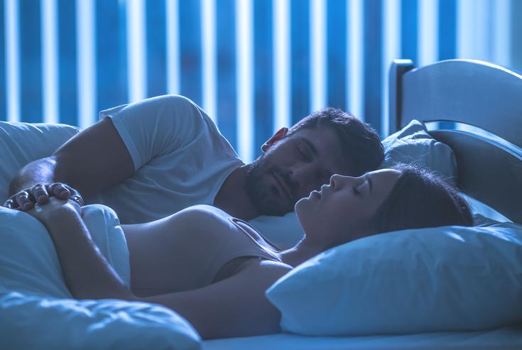 A couple sleeps together.