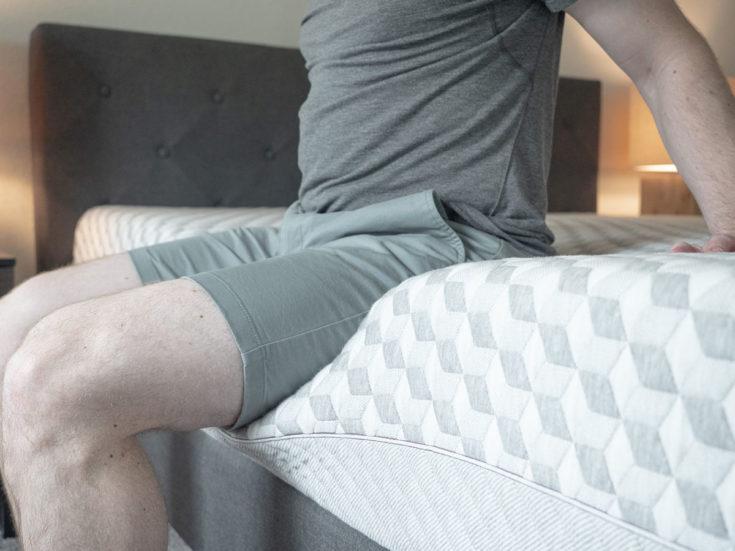 A man sits on the edge of a foam mattress.