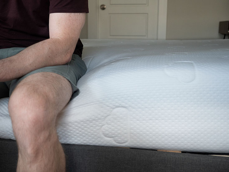 A man sits on the edge of a foam mattress.