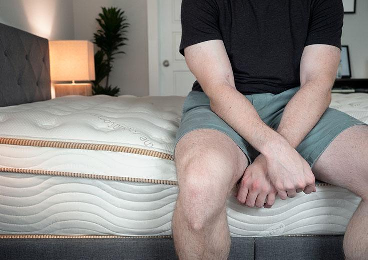 A man is sitting on an innerspring mattress.