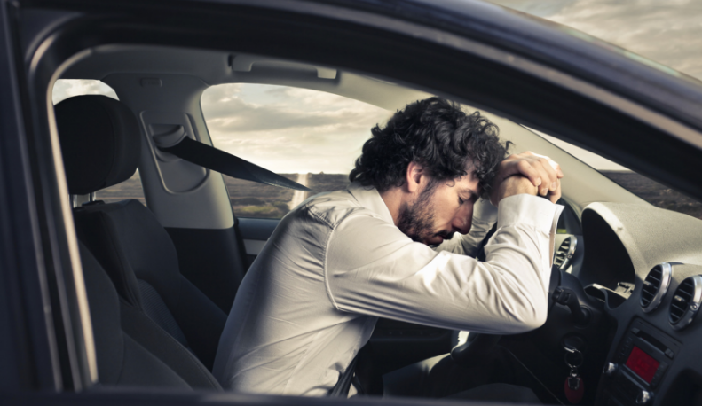 Man falling asleep at wheel of car