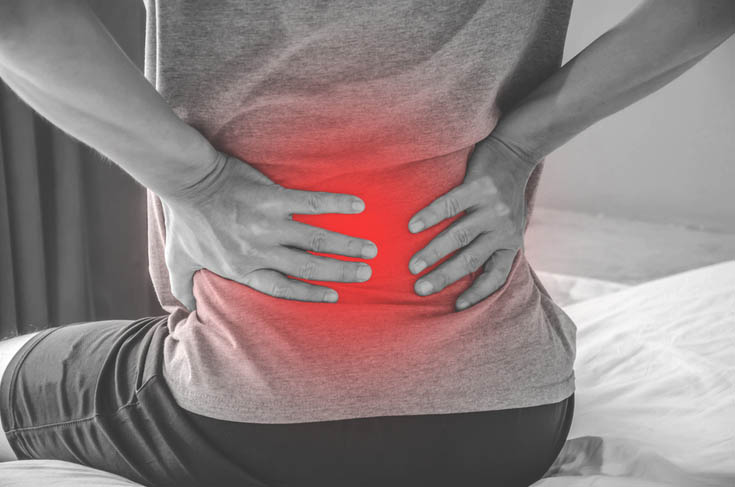 A man holds his lower back because of pain.