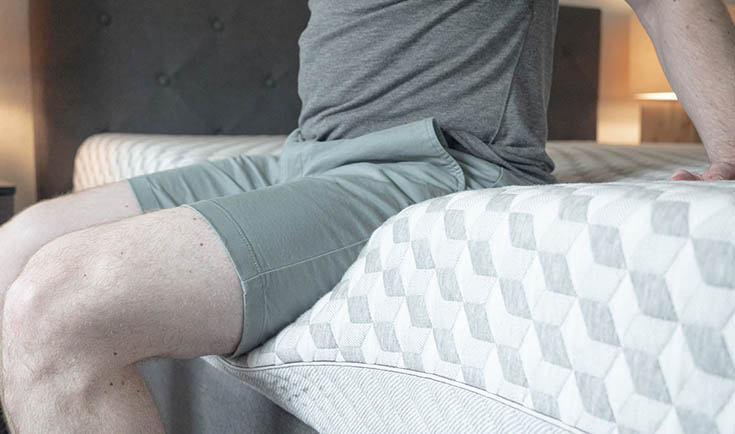 A man sits on his mattress.
