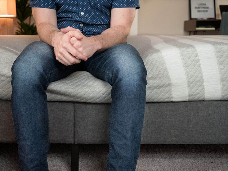 A man sits on the edge of a mattress.