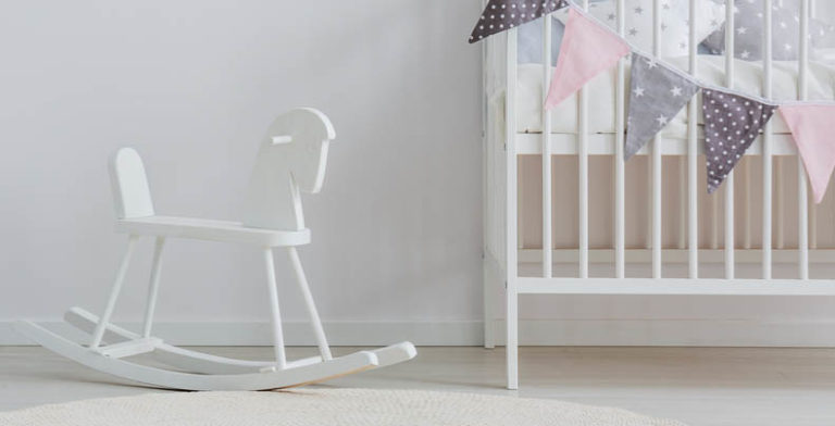 A rocking horse sits next to a crib in a white room.
