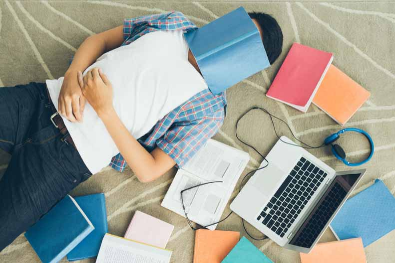 A student sleeps under a book.