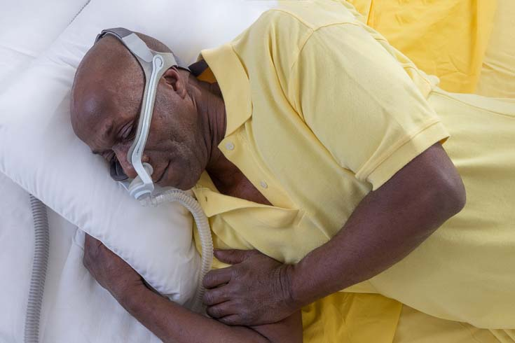 A man sleeps while wearing a CPAP machine.