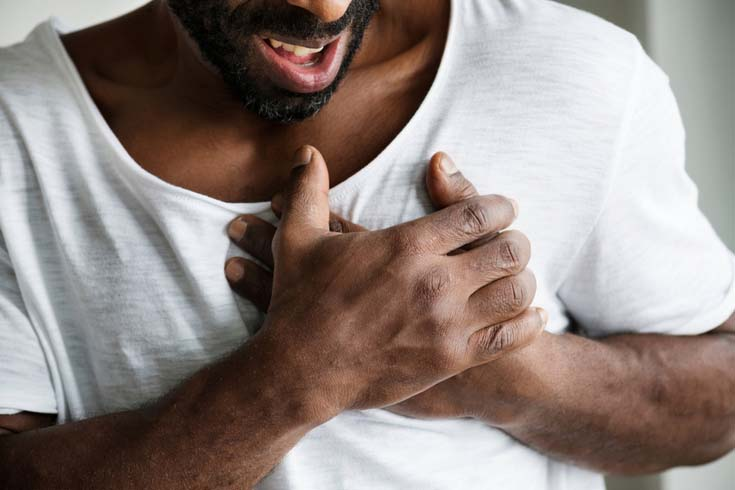 A man grips his heart during an attack.