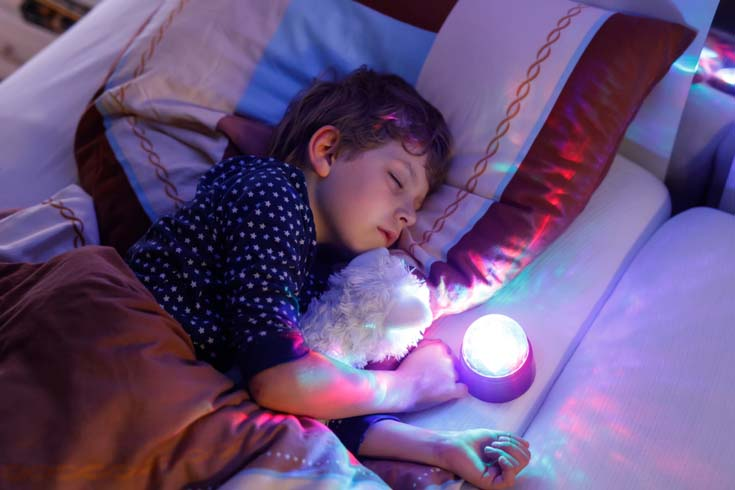 A young kid sleeps with a nightlight.