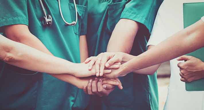 Nurses huddle during a meeting.